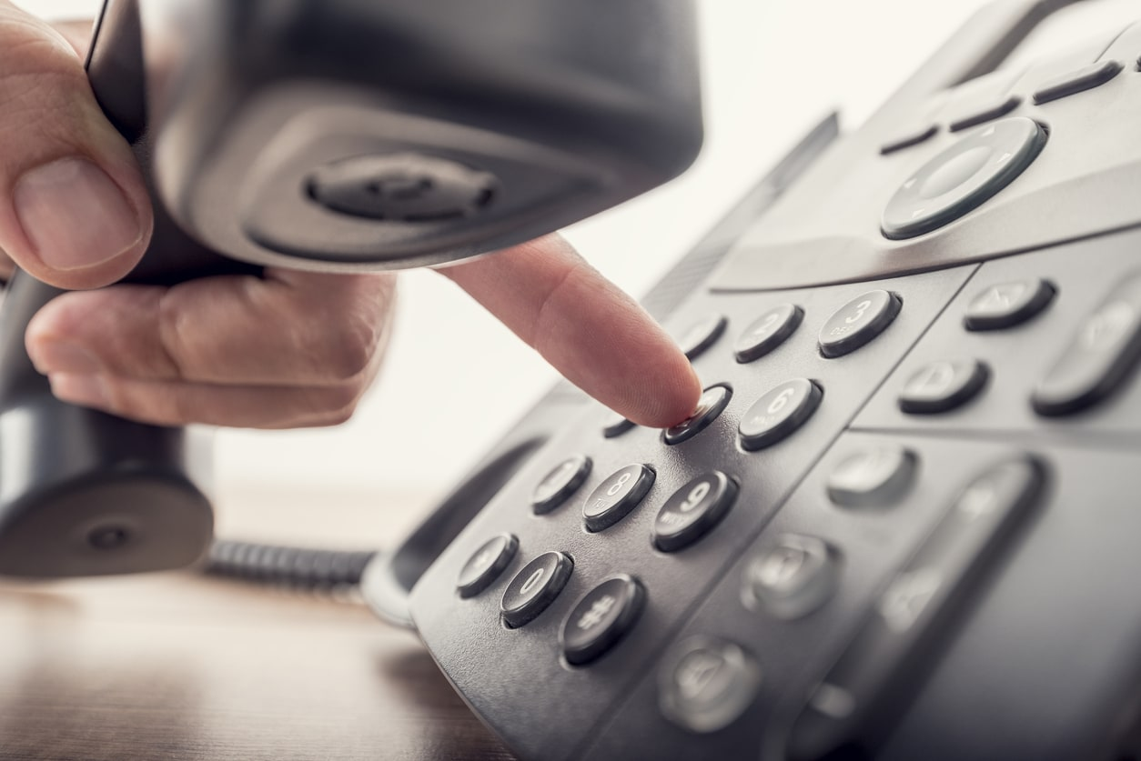 finger dialing a phone number on a landline